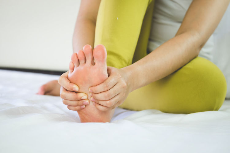 Low section of woman suffering from pain on leg sitting on bed at home