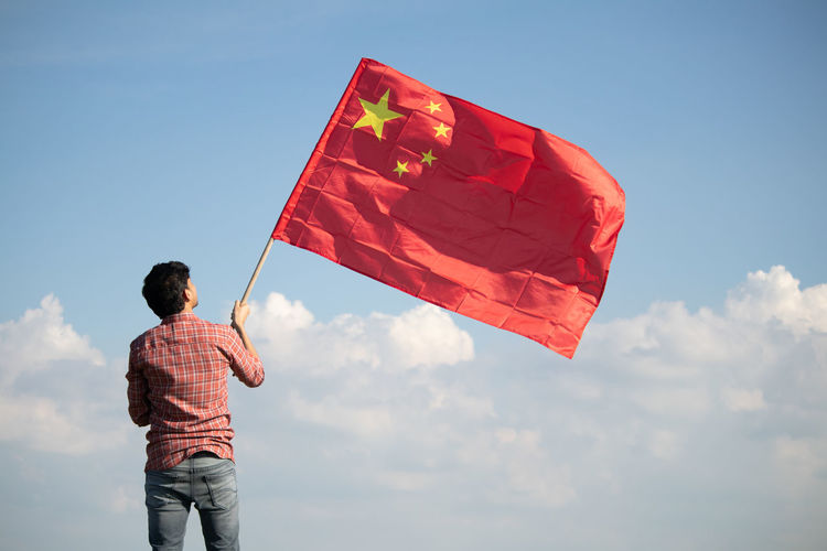 Rear view of man holding chinese flag standing against sky