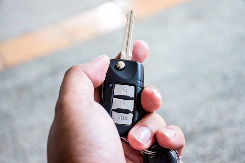 Close-up of person holding car key