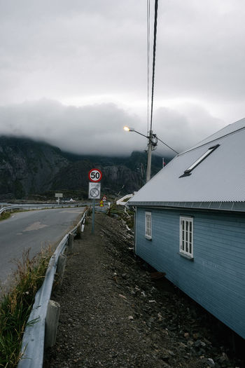 Road sign by mountain against sky