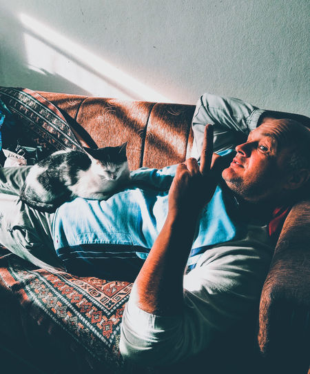 Man with cat lying on sofa at home