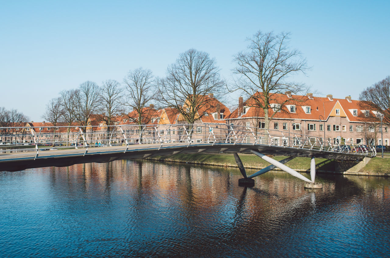 architecture, built structure, water, building exterior, bare tree, tree, river, day, waterfront, outdoors, bridge - man made structure, sky, clear sky, no people, travel destinations, covered bridge, nature