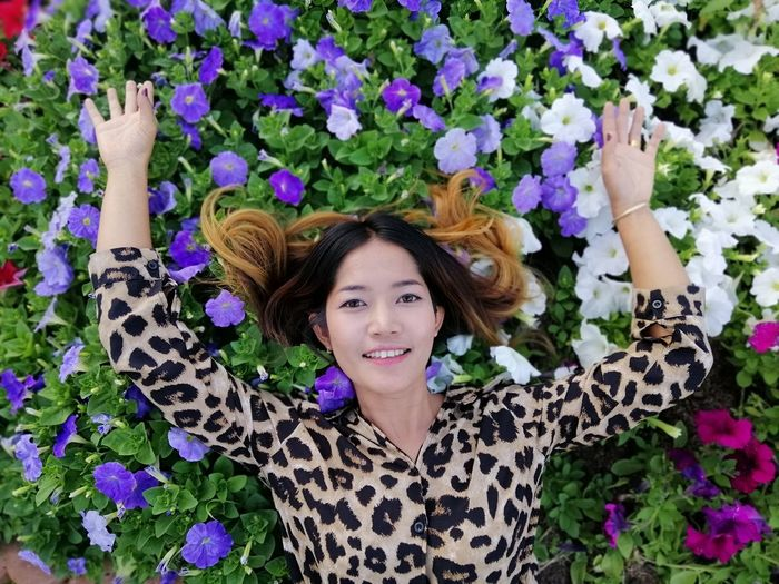 High angle portrait of smiling woman lying on flowers