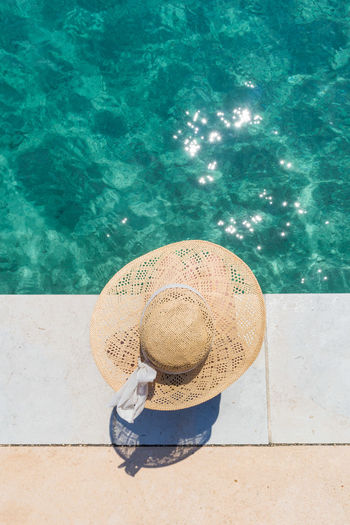Directly above shot of woman wearing hat sitting by sea