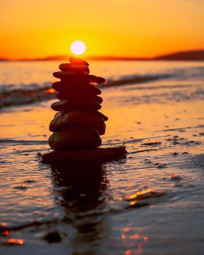Stack of stones in sea during sunset