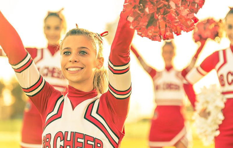 Cheerful cheerleader cheering with friends on field