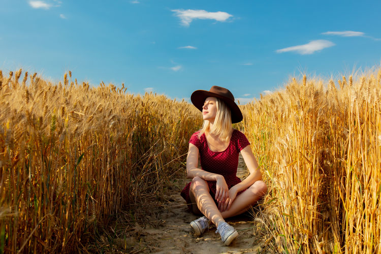 Young woman sitting on field against sky