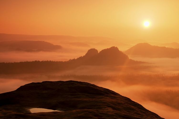Dreamy misty landscape. majestic mountain cut the lighting mist. colorful fog and rocky hills