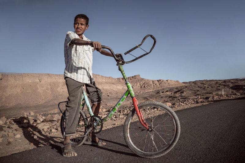 A boy From Djanet Arid Climate Bicycle Boys Casual Clothing Childhood Clear Sky Day Full Length Happiness Leisure Activity Lifestyles Looking At Camera Nature One Person Outdoors People Portrait Real People Sky Smiling Standing Sunlight Transportation Young Adult