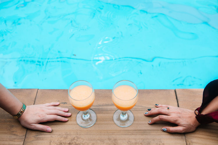 Alcohol Body Part Drink Drinking Glass Food And Drink Freshness Glass Hand Household Equipment Human Body Part Human Hand Leisure Activity Lifestyles People Pool Real People Refreshment Swimming Pool Water