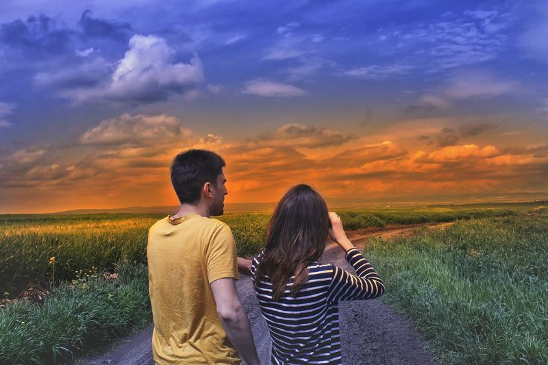 Couple on road amidst field against sky during sunset