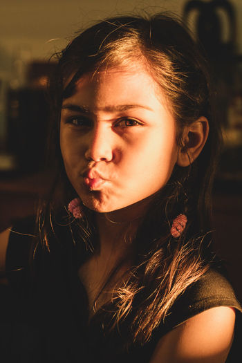 Close-up portrait of girl pouting at home