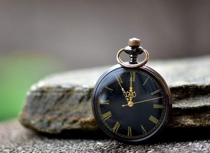 Close-up of vintage clock on rock