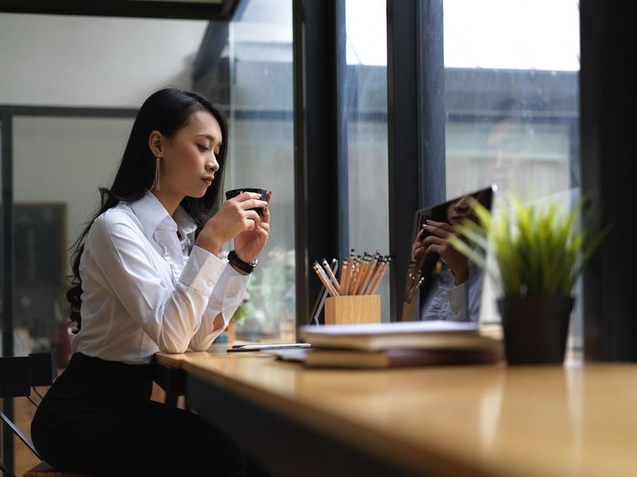 Side view of businesswoman holding coffee cup sitting at office