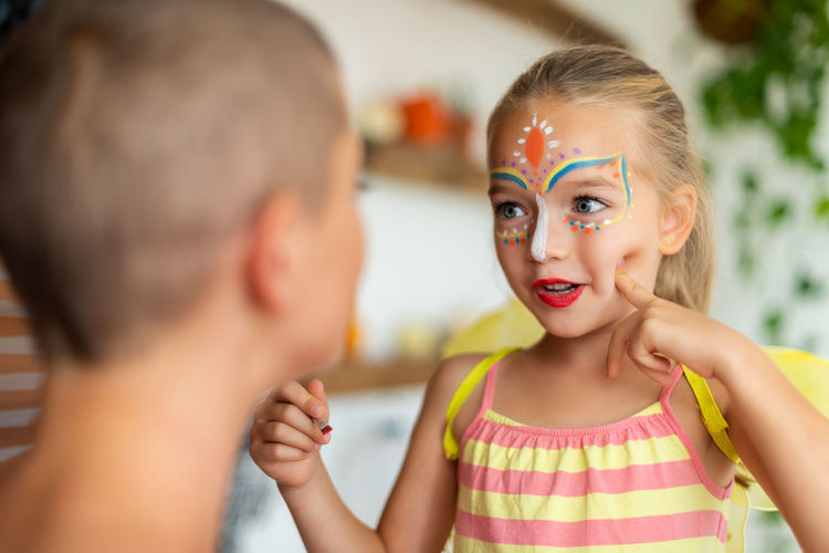 Smiling mother and daughter with face paint sitting at home
