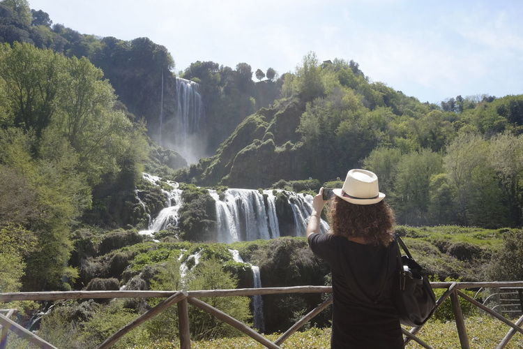 From Behind Hat Woman Waterfall Tree Water Plant Scenics - Nature Nature Motion One Person Beauty In Nature Rear View Day Leisure Activity Flowing Water Real People Adult Clothing Mountain Outdoors Looking At View