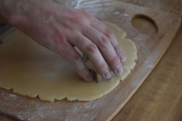 Cropped Image Of Hand Making Cookies With Dough At Table In Kitchen