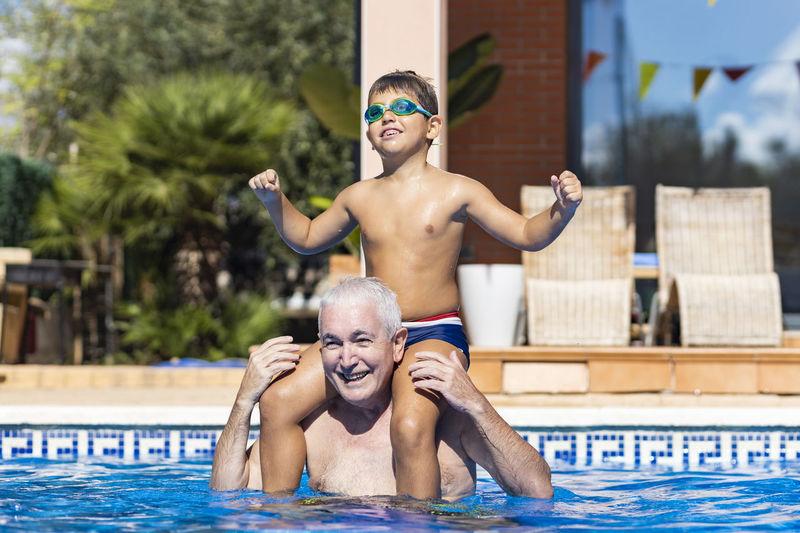 Full length portrait of happy boy in swimming pool