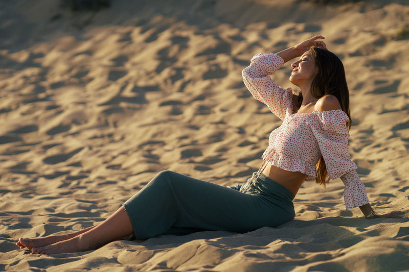 Full length of woman relaxing on sand at beach