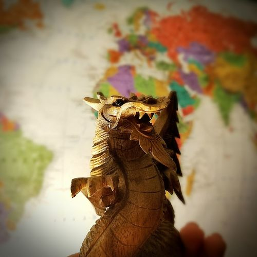 Seek an adventure. Carving Wooden Dragon World Map Vignette Background Travel Reptile Multi Colored Portrait Close-up
