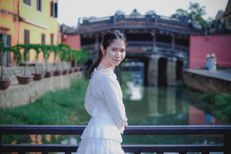 Portrait of smiling young woman standing by railing of bridge over canal