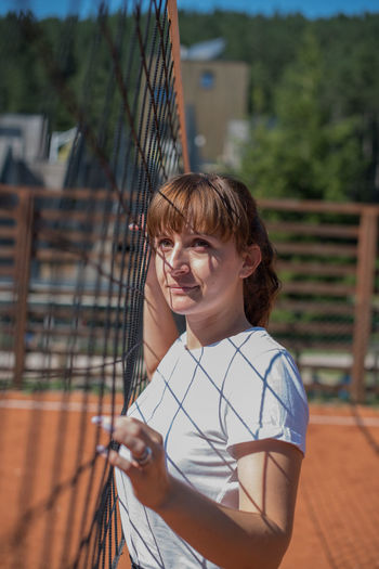 Young woman looking away while standing by net