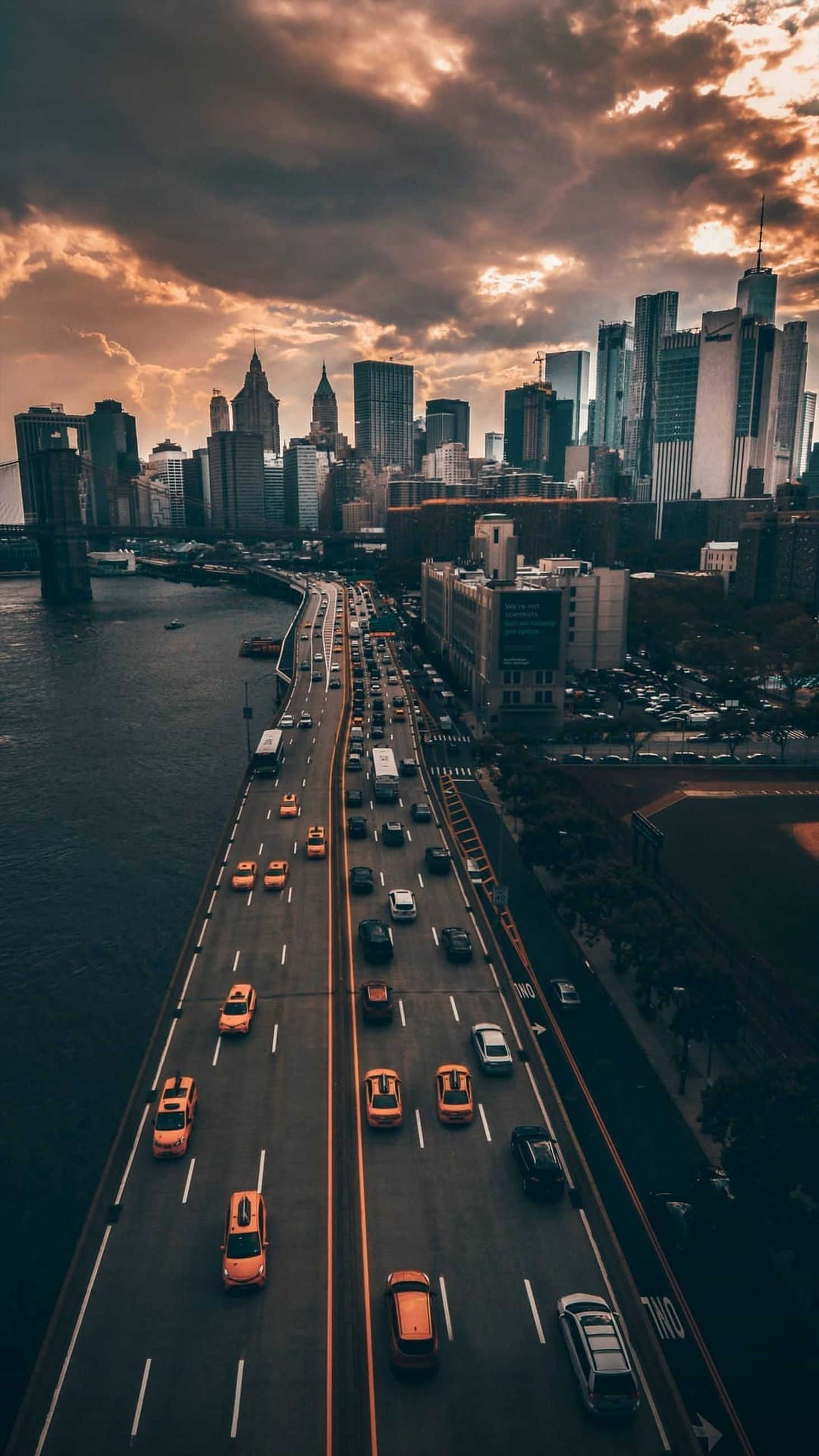 transportation, city, road, car, architecture, sky, motor vehicle, built structure, building exterior, cloud - sky, mode of transportation, sunset, land vehicle, high angle view, symbol, traffic, marking, street, sign, cityscape, no people, office building exterior, outdoors, skyscraper, city street, multiple lane highway, modern