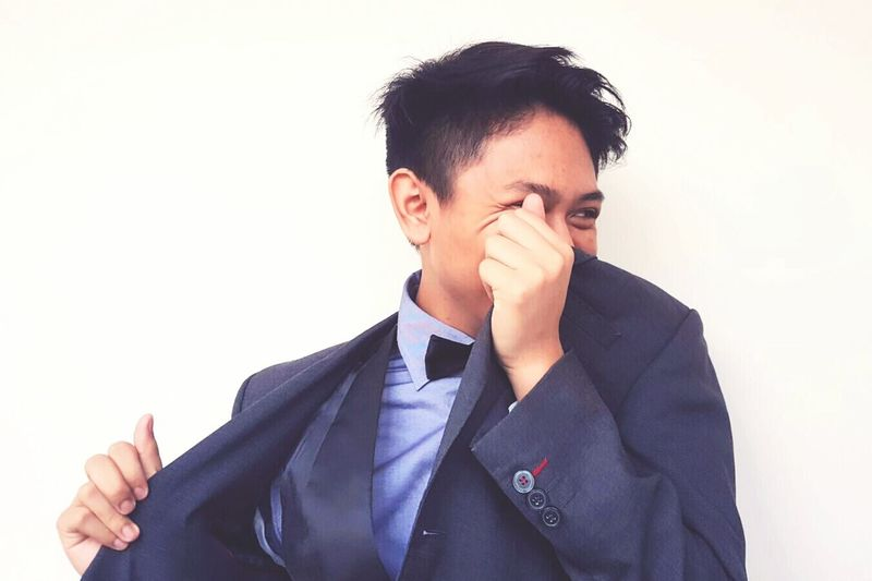 Businessman covering face with suit against wall