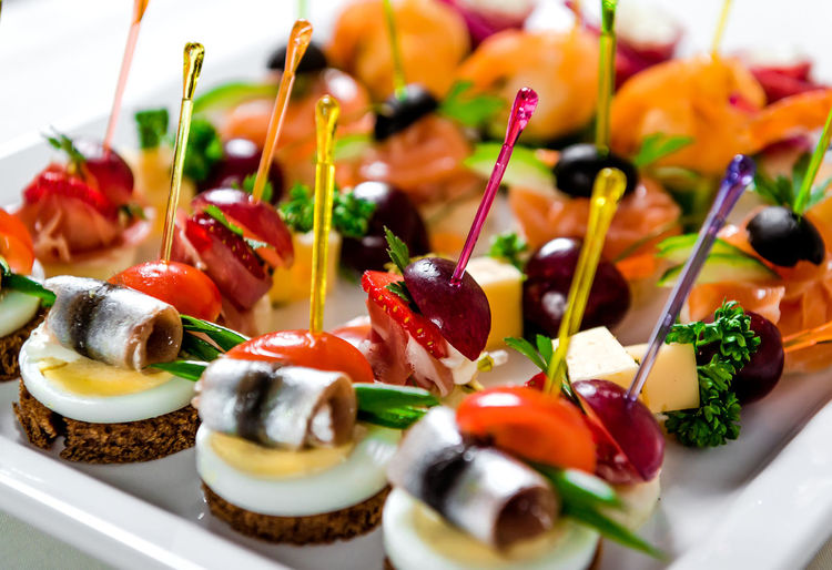 Close-up of various seafood and meat canapes over white background