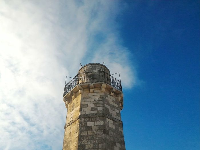 Low angle view of tower against cloudy blue sky on sunny day