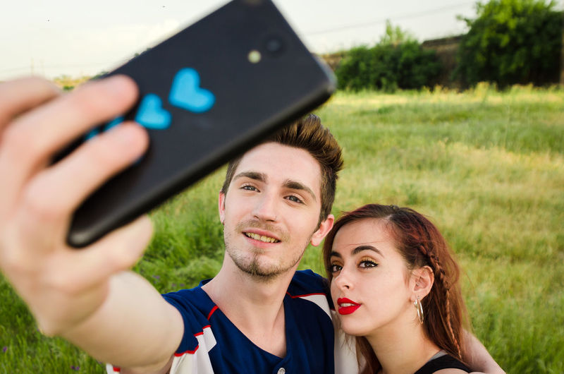 Young couple taking selfie with smart phone on field
