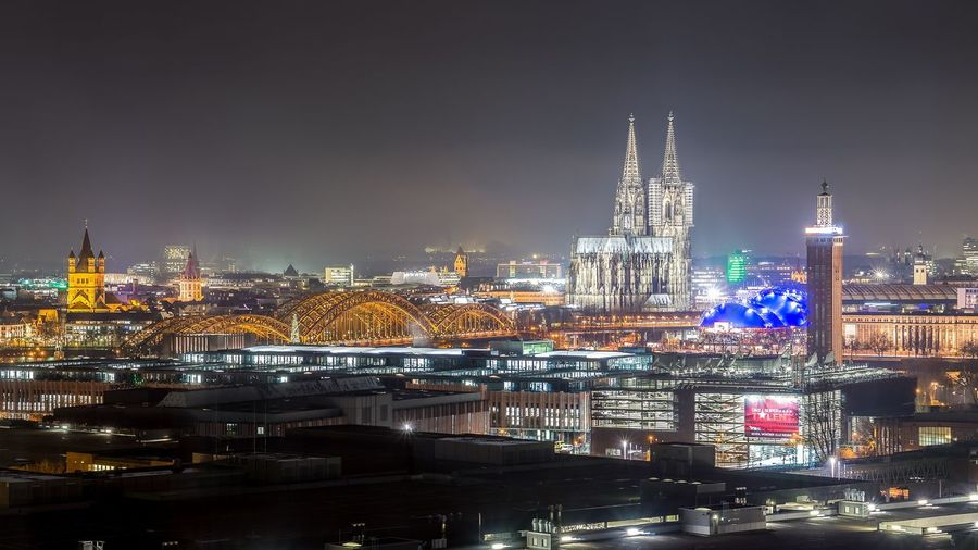 Illuminated cologne cathedral in city against sky at night