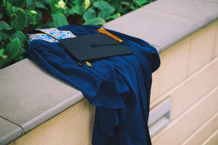 Graduation Gown With Mortarboard On Retaining Wall