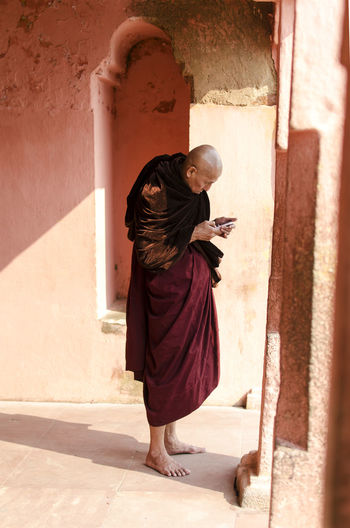 Side view of monk using smart phone while standing against wall
