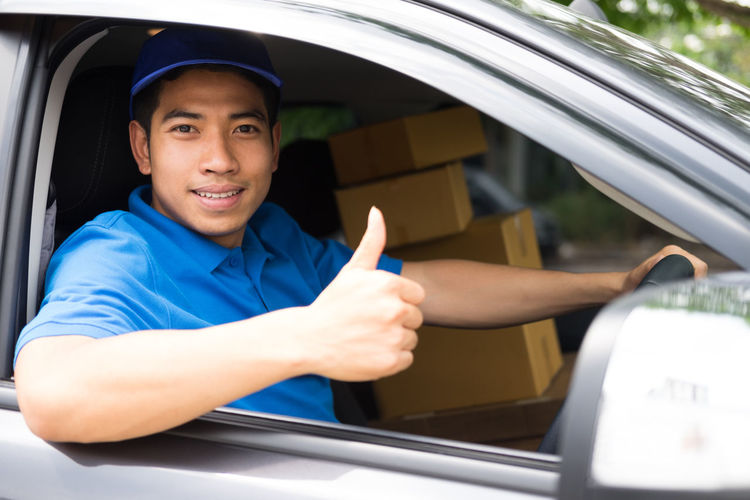 Man with packages gesturing thumbs cup while sitting in car seen through window