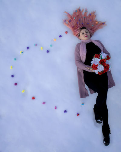 Midsection of woman lying with flowers on snow