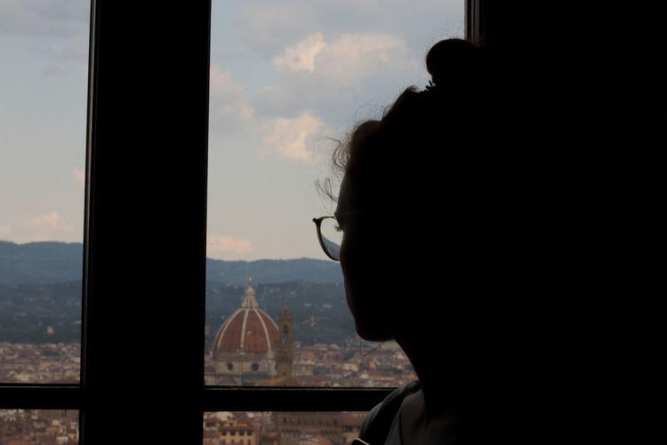 Portrait of silhouette man looking through window