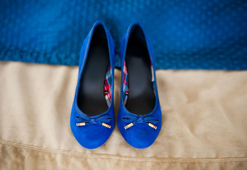 Female elegance bridal blue shoes on beige cloth in horizontal orientation, nobody. Pair of chamois leather wedding shoes with bows. Blue Boot Boots Bow Bridal Bride Chamois Cloth Accessory Elégance Female Feminine  Footgear Footwear Footwears Indoors  No People Pair Shoe Shoes Wedding
