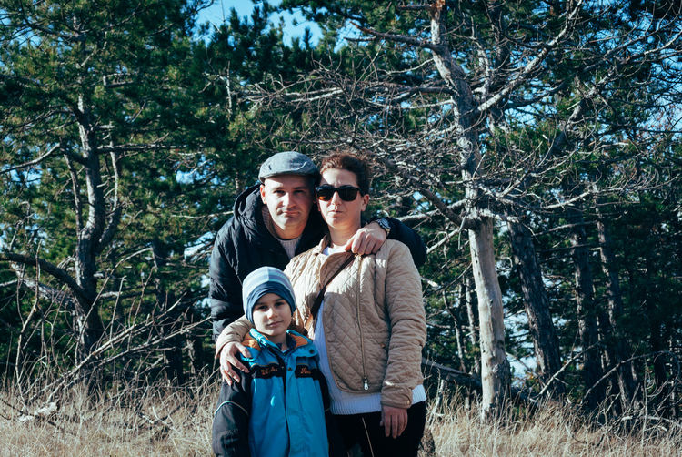 Portrait of family standing against trees at forest