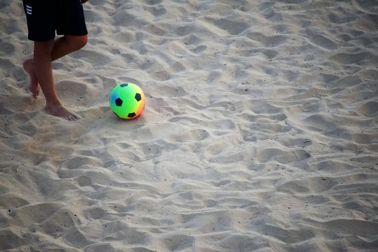 Ball Land Sand Human Leg High Angle View Beach Body Part One Person Low Section Human Body Part Leisure Activity Real People Soccer Soccer Ball Day Nature Team Sport Sport Outdoors Human Limb Football Beach Football On The Beach Copy Space