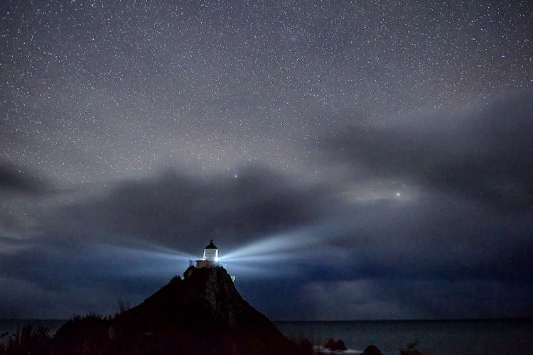 Distance view of lighthouse on mountain against star field at night