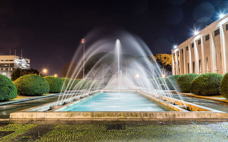 Fountain in city against sky at night