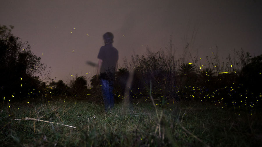 Man standing on field against sky at night