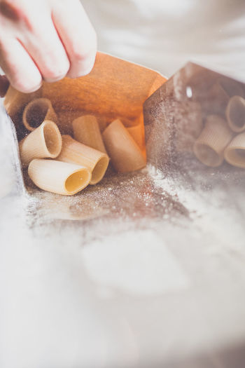 Cropped image of hand packing pasta in factory