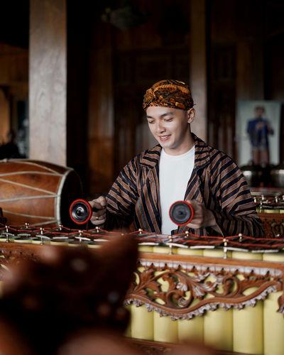 Portrait of boy sitting on stage - gamelan, indonesian javanese traditional music