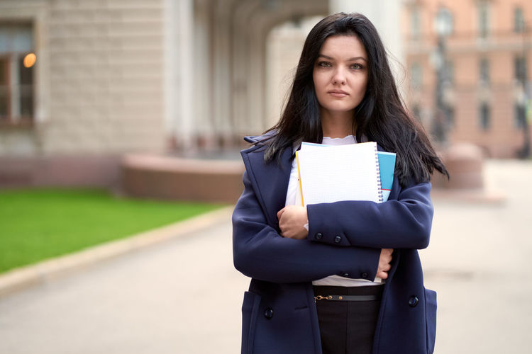 Portrait of young woman holding books outside university