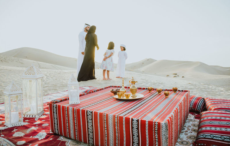 Family standing by carpet on sand dune