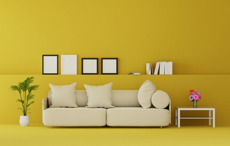 Cushions On Sofa Against Yellow Wall At Home