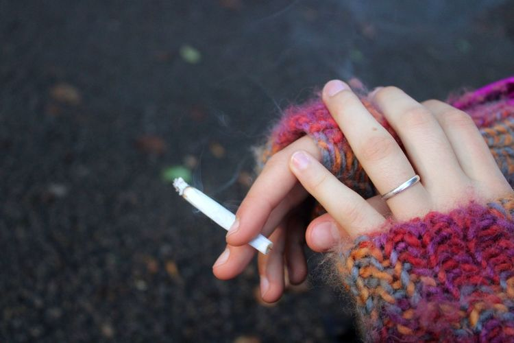 Midsection of woman holding cigarette