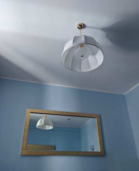 Low angle view of pendant light hanging on ceiling of house